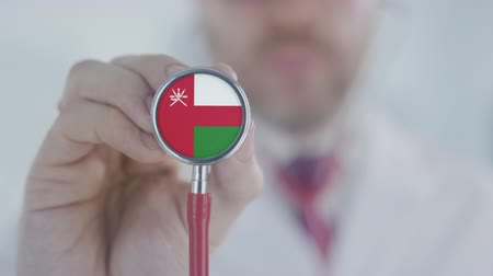 therapeute : Medical doctor holds stethoscope bell with the Omani flag. Healthcare in Oman Vidéos Libres De Droits