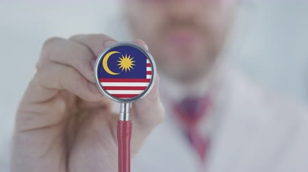 diagnóstico : Doctor listening with the stethoscope with flag of Malaysia. Malaysian healthcare Stock Footage
