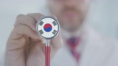 diagnóstico : Doctor uses stethoscope with the South Korean flag. Healthcare in South Korea Stock Footage