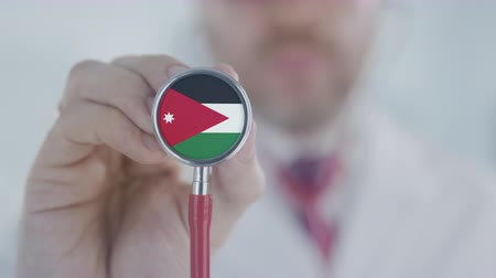 diagnóstico : Doctor listening with the stethoscope with flag of Jordan. Jordanian healthcare