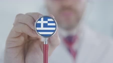 terapeuta : Physician uses stethoscope with the Greek flag. Healthcare in Greece Stock Footage
