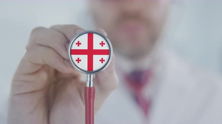 diagnóstico : Doctor holds stethoscope bell with the Georgian flag. Healthcare in Georgia