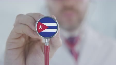 diagnóstico : Doctor holds stethoscope bell with the Cuban flag. Healthcare in Cuba