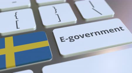 İsveççe : E-government or Electronic Government text and flag of Sweden on the keyboard. Modern public services related conceptual 3D animation