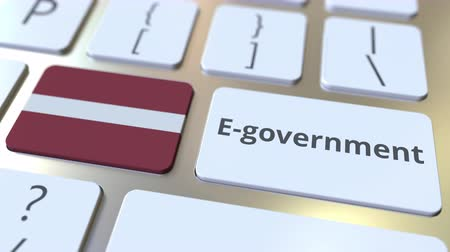 involvement : E-government or Electronic Government text and flag of Latvia on the keyboard. Modern public services related conceptual 3D animation
