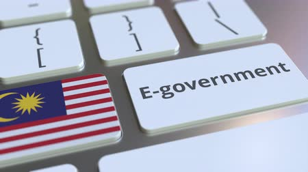 malásia : E-government or Electronic Government text and flag of Malaysia on the keyboard. Modern public services related conceptual 3D animation