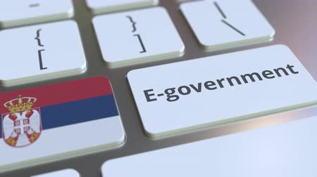 involvement : E-government or Electronic Government text and flag of Serbia on the keyboard. Modern public services related conceptual 3D animation Stock Footage