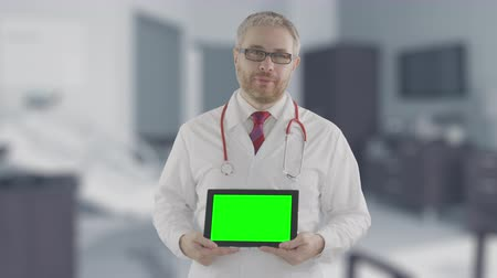 personalizado : Portrait of a confident doctor holding modern tablet PC with green screen, shot on Red camera. Alpha matte for picture or video placement