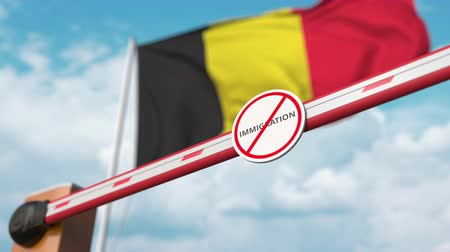 göçmen : Barrier gate with no immigration sign being opened with flag of Belgium as a background. Belgian immigration approval