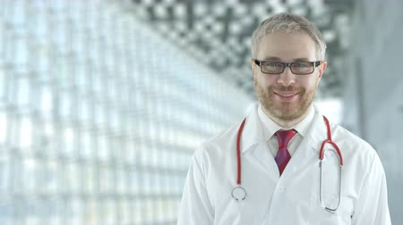 очки : Portrait of a smiling assuring doctor in the modern hospital hall. Shot on Red camera Стоковые видеозаписи