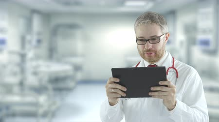 очки : Cheerful doctor uses portable tablet PC for telemedicine communication session with a patient. Shot on Red camera