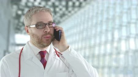 laboratorium : Doctor wearing glasses talks to patient on his smartphone. Shot on Red camera