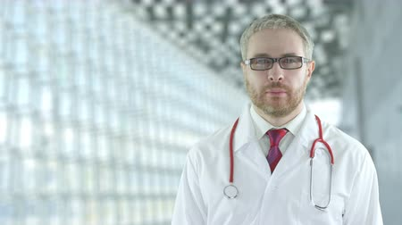 очки : A calm focused doctor in the modern hospital hall. Shot on Red camera