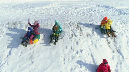 szánkó : The children are playing and rolling down a hill on snow inflatable sled. Slow motion video Stock mozgókép
