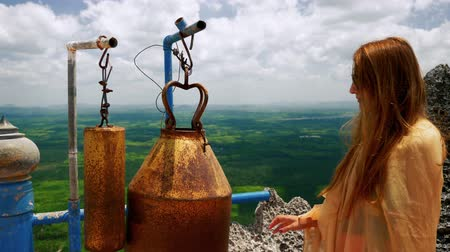 Girl ringing bells at buddhist temple on the top of the mountain.