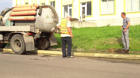 sewerage worker on street cleaning pipe, sewerage repair diver Lutsk Ukraine 08012018