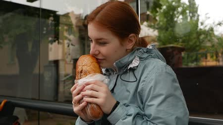 lado : Happy red-haired girl eats a loaf at the bus stop