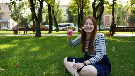 saçlı : Red-haired girl blows soap bubbles in the park.She smiling and laughing.summer and happiness