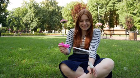 vöröshajú : Red-haired girl blows soap bubbles in the park.She smiling and laughing.summer and happiness