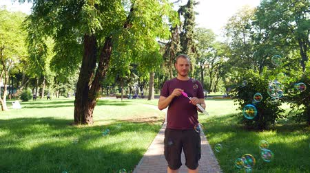 výstřední : Guy with a beard blows soap bubbles. In the park a sunny day