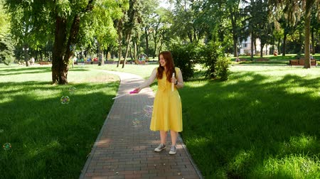 saçlı : Red-haired girl blows soap bubbles in the park.yellow dress Stok Video
