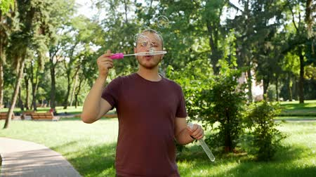 легкий : Guy with a beard blows soap bubbles. In the park a sunny day