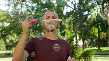 különc : Guy with a beard blows soap bubbles. In the park a sunny day