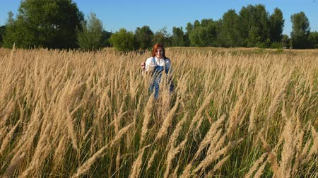 saçlı : red-haired girl in blue overalls in a field of spikelets Stok Video