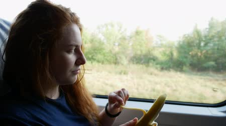 banan : Girl eats a banana by the window of the train Wideo