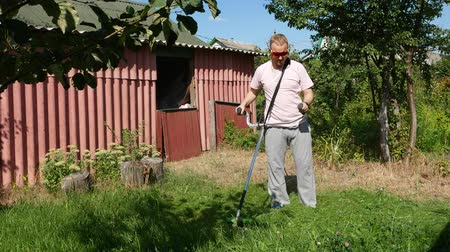 mow : A guy in a pink T-shirt mows the grass with an electric scythe