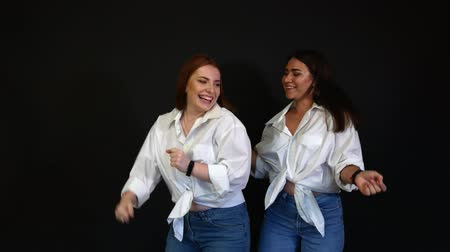 saçlı : Girls in white shirts dancing and fooling around on a black background