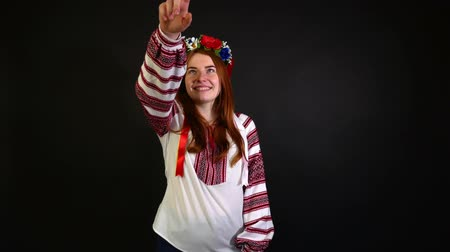 saçlı : Cheerful red-haired girl in an embroidered shirt draws a word in the air and smiles. Black background