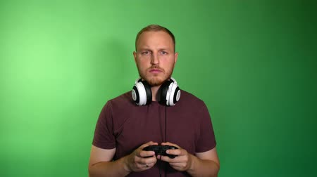 ひげを剃っていない : Focused man in removed headphones plays console