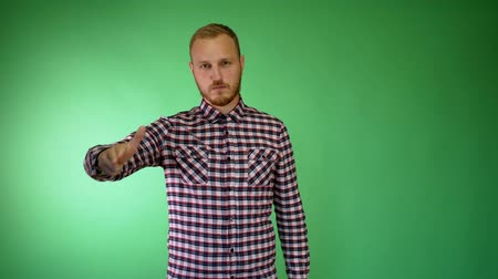 мрачный : Sad bearded young man. Plaid shirt. Hand like a gun. Suicide concept. Head shot.
