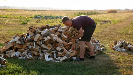 material body : A man carries firewood with his hands in the village
