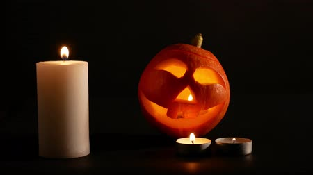 hallows : Carved Halloween pumpkin lights inside with flame. black background lighted candles close up.