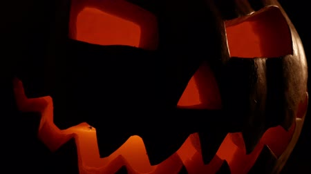 hallows : spooky jack-o-lantern or carved pumpkin lantern burning in darkness. halloween and holidays concept Stock Footage