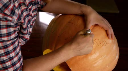 hacı : A man carves a Halloween pumpkin. A knife in his hands. Stok Video