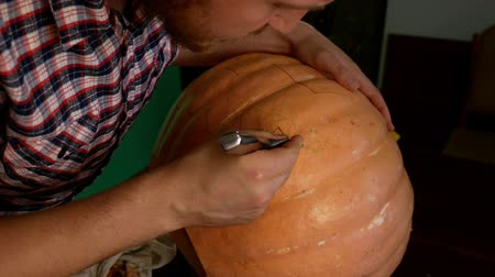 seu : A man carves a Halloween pumpkin. A knife in his hands. Vídeos