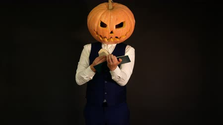 hloupý : carved pumpkin. a man with a pumpkin head turns the pages of a book. Halloween concept. Dostupné videozáznamy