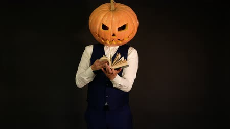 hloupý : a man with a pumpkin head turns the pages of a book. Halloween concept.carved pumpkin.