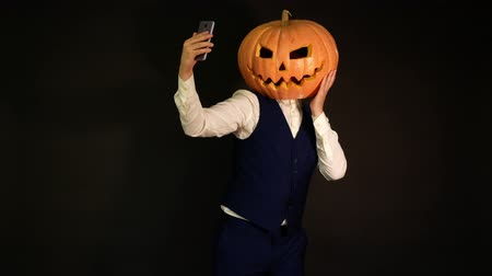 oco : carved pumpkin. man with pumpkin head takes selfie. Halloween concept. Stock Footage