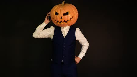 hloupý : pumpkin-headed man talking on the phone. Halloween concept.carved pumpkin.