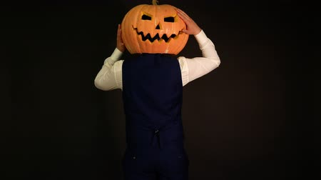 hloupý : a man with a pumpkin head lost his face but found it on the back of his head. Halloween concept.carved pumpkin.