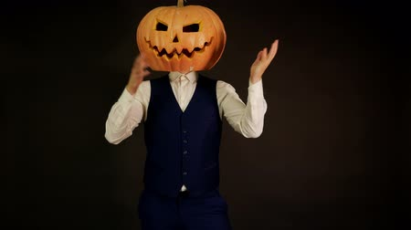oco : carved pumpkin. pumpkin-headed man clutching his head with his hands. Halloween concept