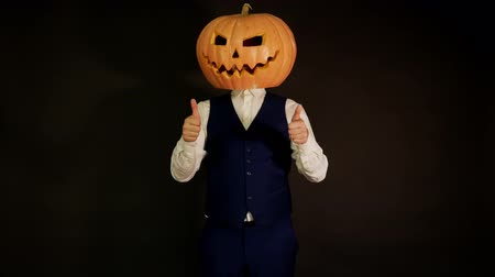 hloupý : carved pumpkin. pumpkin-headed man raises his finger up. Halloween concept.