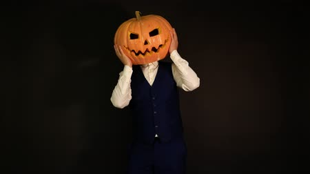 oco : pumpkin-headed man clutching his head with his hands. Halloween concept.carved pumpkin.