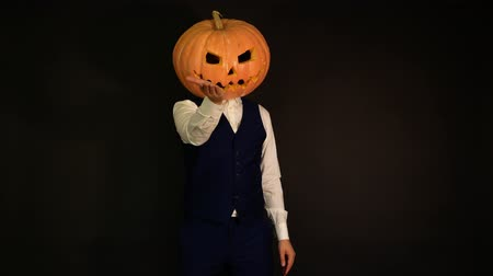 oco : carved pumpkin. a pumpkin-headed man sends and catches a kiss. Halloween concept.