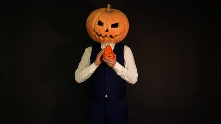 oco : carved pumpkin. pumpkin-headed man stroking his friends pumpkin. Halloween concept.