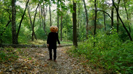 острый : Scary pumpkin-headed man chasing after someone in the forest. Knife in hands. Halloween concept.4k